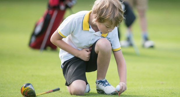 Young boy placing golf ball on tee