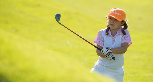 Girl holding golf club after hitting ball at Howley Hall GC