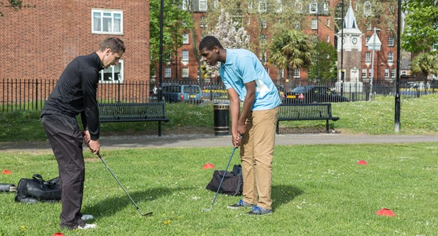 Coach and young man play StreetGolf in Tower Hamlets