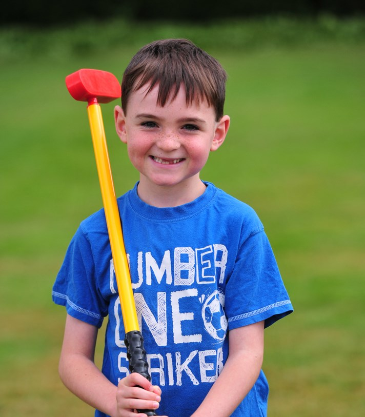 Boy smiling and holding Tri-Golf club