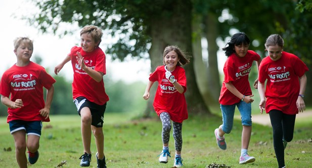 Children running to camera wearing HSBC Golf Roots t-shirts