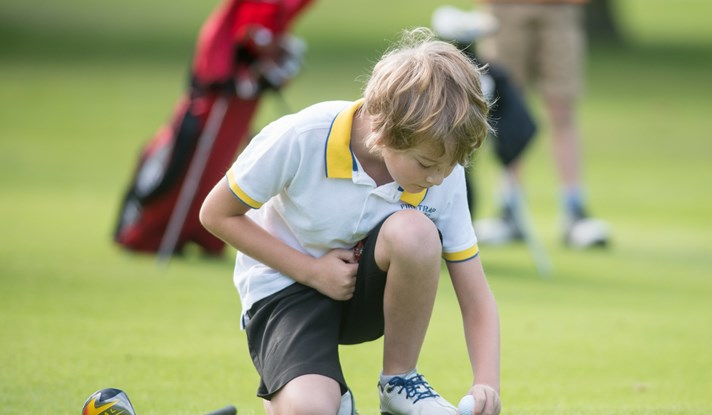 Boy balancing boy on golf tee
