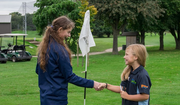 Girls shaking hands at flag at Hatchford Brook Golf Centre