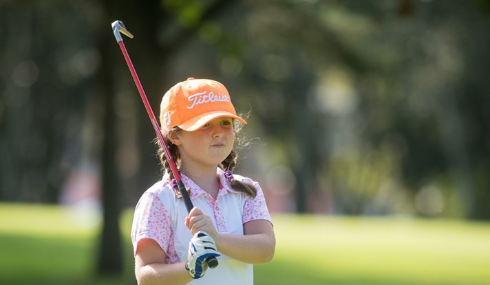 Girl holding golf club (wearing Titleist hat)
