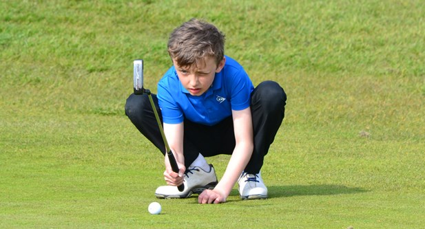 Boy crouching down by golf ball at Cookridge Hall GC