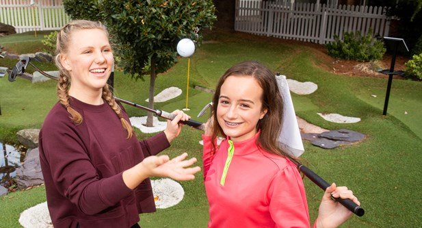 Smiling girls with golf clubs.jpg